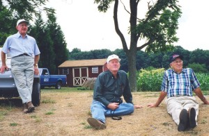 Dad standing with Bill Flick and Uncle Bill sitting - watching a windmill being built.